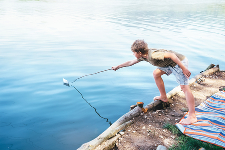 Boy launches the paper boat in lake