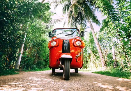 Weligama, Sri Lanka – December 27, 2017: Red tuk-tuk under the palm trees on the country road in Weligama, Sri Lanka Stock Photo
