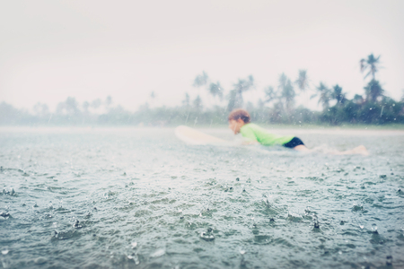 Boy learning to surf under the tropical rain