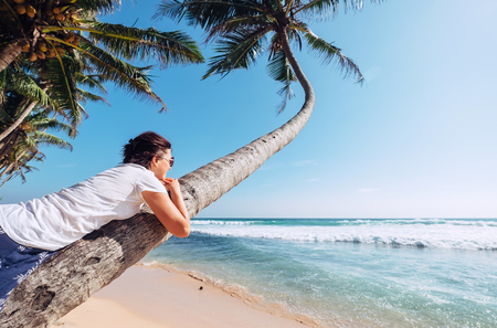 Woman lies on the palm tree and looks on ocaen waves. Summer vacation concept image Stock Photo