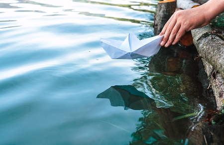 Child hand with paper boat close up image