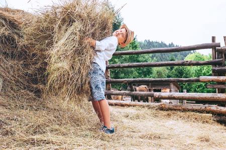 Boy helps on farm. Brings the hay for farm animals