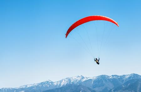 Sportif en parapente rouge planant au-dessus des sommets enneigés des montagnes Banque d'images