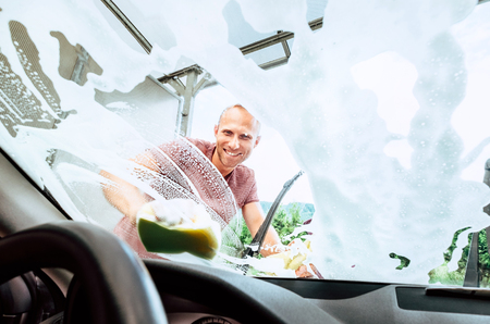Man washes his car front window inside the car camera view Reklamní fotografie
