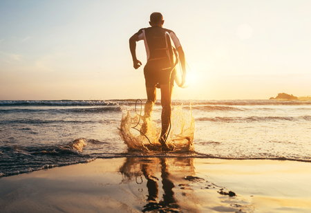 Surfer with surfboard runs in to the ocean waves Stock Photo