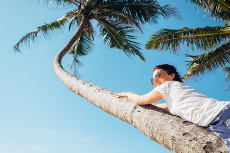 Woman lies on the palm tree. Summer vacation concept image Stock Photo