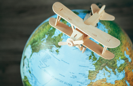 Wooden plane model is on the earth globe. Travel concept image