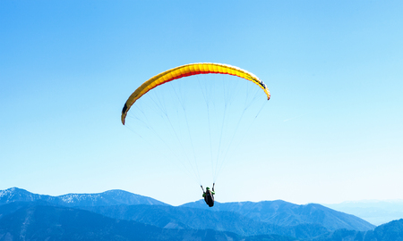 Paraglider soaring in the sky over the blue mountains Zdjęcie Seryjne