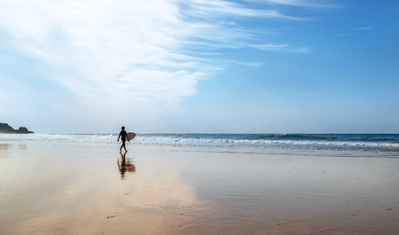 Figura de surfista con tabla de surf en la costa a la hora de la mañana Foto de archivo