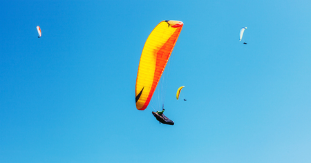 Air sportsmans group soaring in sky with a bright paraplanes