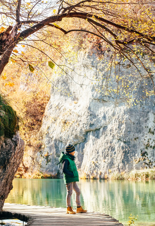 Weekend walk in autumn park: boy stay on wooden bridge near the mountain lake Banco de Imagens