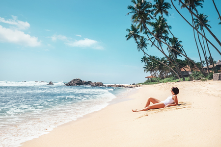 Woman takes sunbath on tropical beach. Island paradise Stockfoto - 104706319