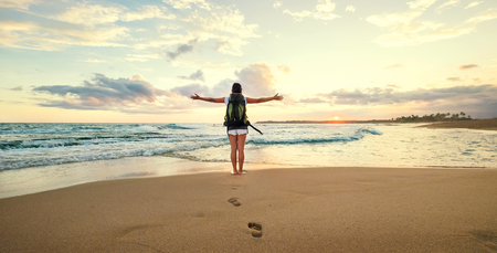 Woman backpacker greeting a sunset at the ocean coast