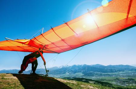 Mann mit dem Hängegleiter, der beginnt, von der Bergspitze zu fliegen Standard-Bild - 104706351