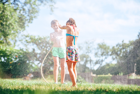 Two childs brother and sister play with watering hose in summer garden