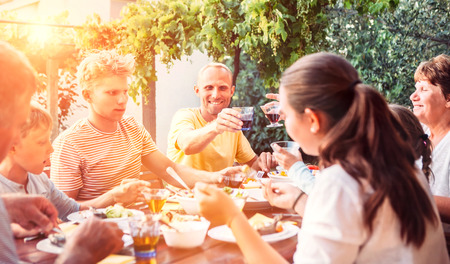 Big family have a dinner on open air in summer garden Imagens