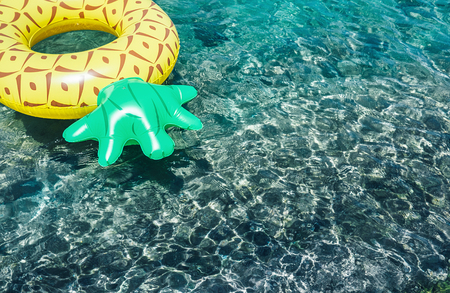 Crystal clear water in the sea lagoon with bright inflatable pineapple pool ring Imagens