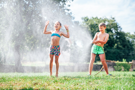 Two child, brother and sister, play with watering hose in hot summer afternoon Stock Photo
