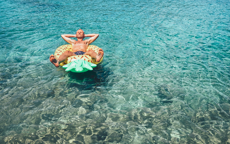 Man has relax time when swims on inflatable pineapple pool ring in crystal clear sea water