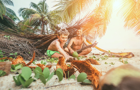 Playing in Robinzones: father and son built a hut from palm tree branches