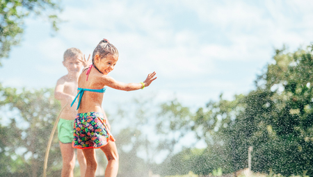 Two children play with sprinkling water in summer garden