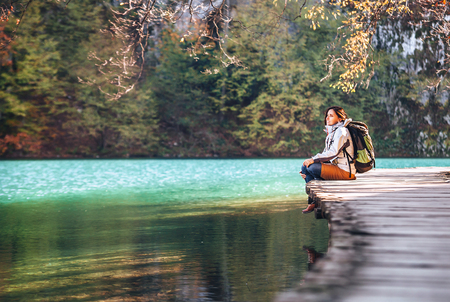 Woman traveler sits on wood bridge on mountain lake at sunny autumn day Фото со стока
