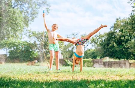 Gelukkige kinderen dollen in de zomertuin, opspattend water en springen Stockfoto