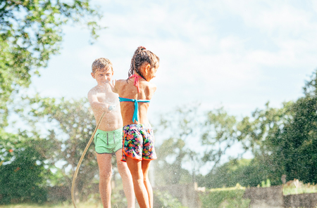 Brother sptays his slittle sister water from garden hose. Children have fun in hot summer day