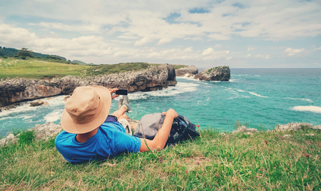 Backpacker traveler rests on the rocky sea side and take mobil photo of beautiful sea landscape