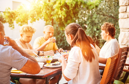 Big family have dinner on open garden terrace