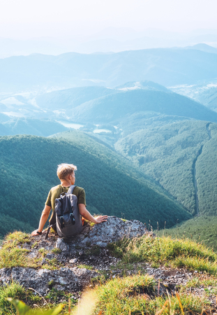 Young man tourist rest on the top of hill with beautiful valley panorama