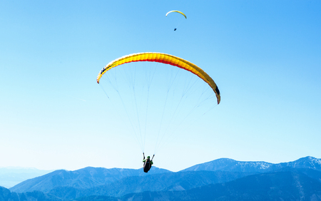 Two Paragliders soaring in the sky over the blue mountains Stock Photo