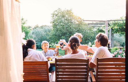 Big family have a dinner. Summer evening in the garden Imagens