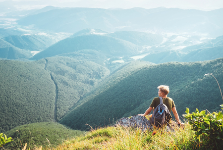 Young man tourist sits on top on hill with beautiful valley panorama