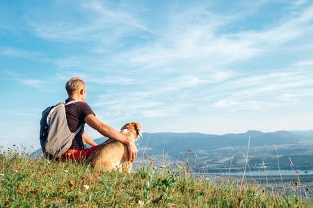 Mężczyzna ze swoim psem rasy beagle siedzi na szczycie wzgórza nad górską doliną Zdjęcie Seryjne