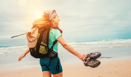 Girl backpacker traveler enjoys with fresh ocean wind