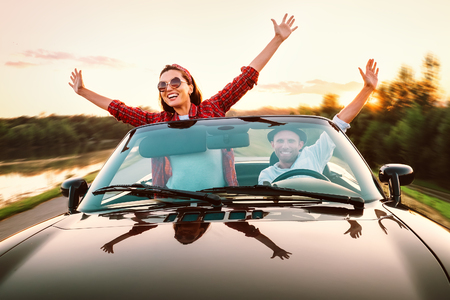 Traveling by car - happy couple in love go by cabriolet car in sunset time Stock Photo