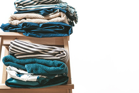 Towels, blankets and other home textile in blue and beidge colors are on the stool