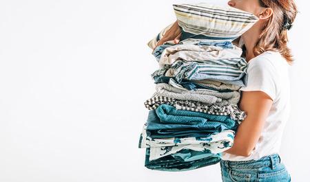 Femme prend en mains gros tas de couvertures bleu et beige, serviettes et autres textiles de maison