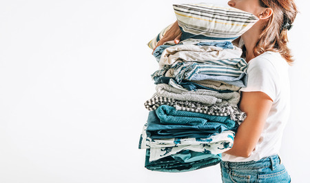 Woman takes in hands big pile blue and beige blankets, towels and other home textile Archivio Fotografico