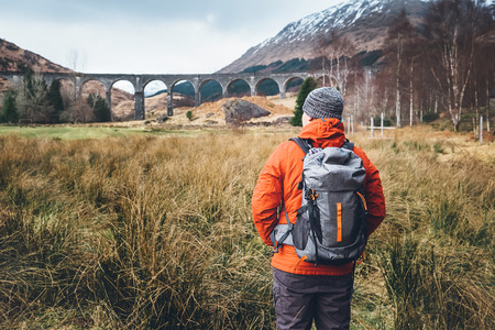 Hiking, walk with backpack, active lifestyle concept image. Man traveler walks neaar famous Glenfinnan viadukt in Scotland