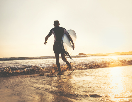 Surfer with surfboard runs in ocean waves, sunset time. Active lifestyle concept Stock Photo