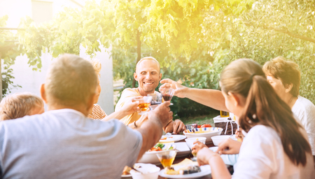 Family have dinner in summer garden Imagens