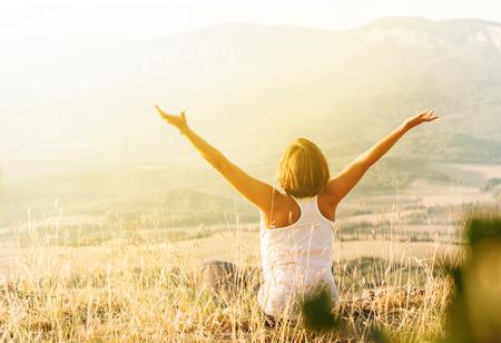 Woman meets sunrise in mountain