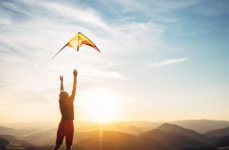 Mann fängt an, einen Drachen in den Himmel zu fliegen Standard-Bild - 107564882