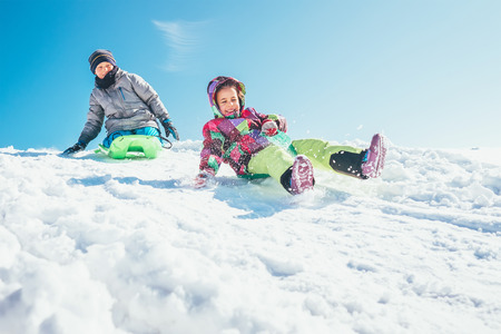 Brother and sister slide down from the snow slope. Winter time pleasures Stock Photo