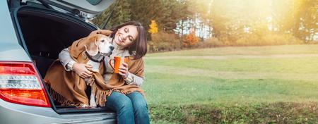 Femme huges son chien avec des châles assis ensemble dans le coffre de la voiture Banque d'images