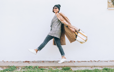 Happy smiling woman walk on the street. Multilayered style fashion outfit