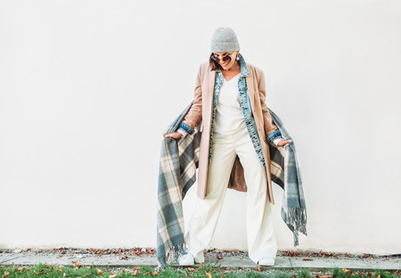 Woman dressed in multilayered autumn outfit: camel coat, denim jacket and elegant trousers