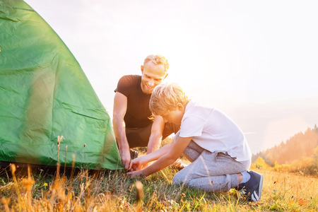 Father helps his son setting tent on sunset forest glade